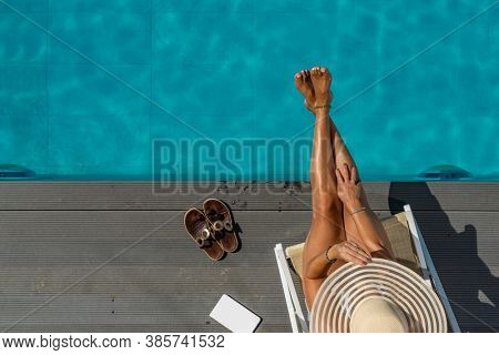 woman sitting on a deck chair at luxury five stars  spa resort by the swimming pool.