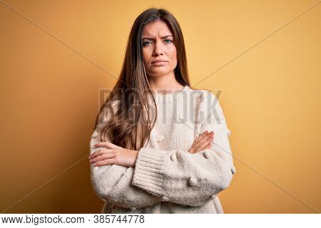 Young beautiful woman with blue eyes wearing casual sweater standing over yellow background skeptic and nervous, disapproving expression on face with crossed arms. Negative person.