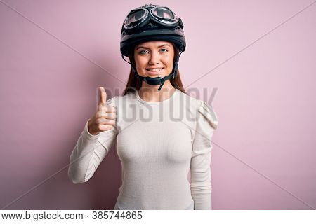 Young beautiful motorcyclist woman with blue eyes wearing moto helmet over pink background doing happy thumbs up gesture with hand. Approving expression looking at the camera showing success.