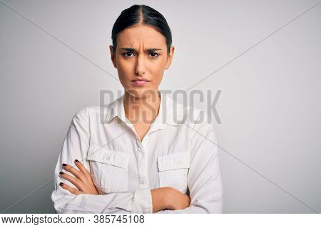 Young beautiful brunette woman wearing casual shirt over isolated white background skeptic and nervous, disapproving expression on face with crossed arms. Negative person.