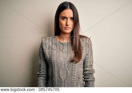 Young beautiful brunette woman wearing casual sweater over isolated white background skeptic and nervous, frowning upset because of problem. Negative person.