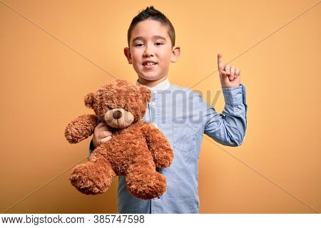 Young little boy kid hugging teddy bear stuffed animal over yellow background surprised with an idea or question pointing finger with happy face, number one