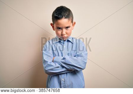 Young little boy kid wearing elegant shirt standing over isolated background skeptic and nervous, disapproving expression on face with crossed arms. Negative person.