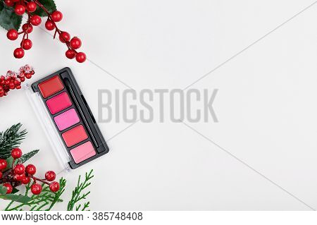 Christmas Make-up Beauty Product On A Gray Background Top View. Holly Holiday Composition With Red L