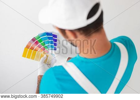 High Angle Back View Of Professional Male Painter Holding Colorful Palette While Standing Against Wh