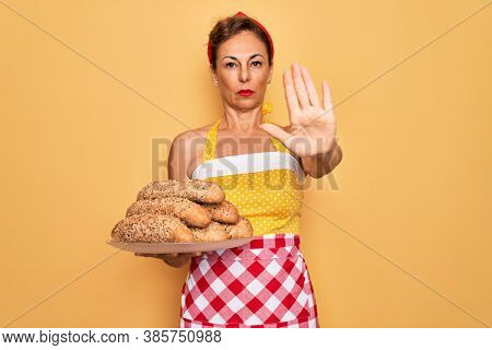 Middle age senior housewife pin up woman wearing 50s style retro dress cooking wholemeal bread with open hand doing stop sign with serious and confident expression, defense gesture