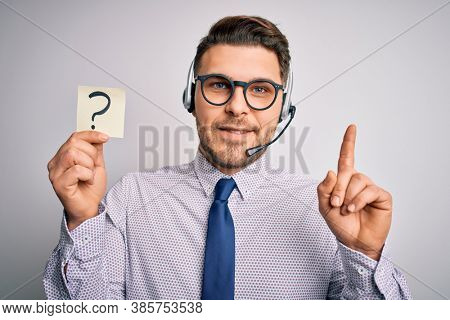 Young call center operator business man with blue eyes holding paper note with question mark surprised with an idea or question pointing finger with happy face, number one