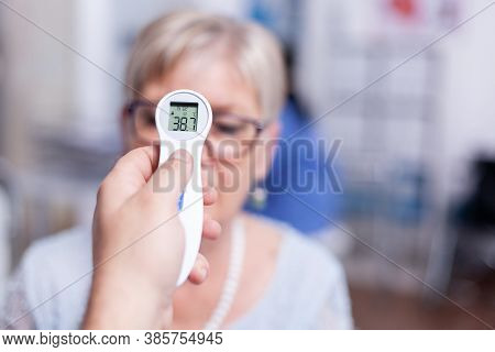 Reading Body Temperature Using Infrared Thermometer During Medical Examination. Consultation For Inf