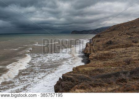 A Desolate Coast Of A Turbid Stormy Black Sea Under Gloomy Dark Clouds In The Crimea