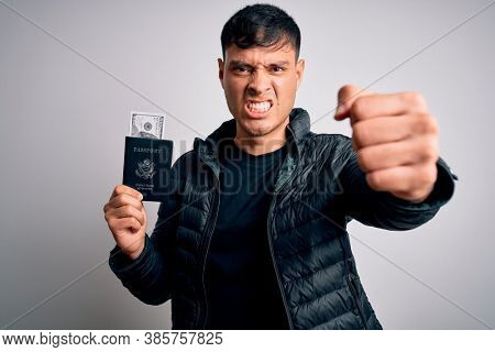 Young hispanic man holding passport document with money over isolated background annoyed and frustrated shouting with anger, crazy and yelling with raised hand, anger concept