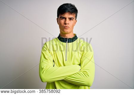 Young handsome sportsman doing sport wearing sportswear over isolated white background skeptic and nervous, disapproving expression on face with crossed arms. Negative person.