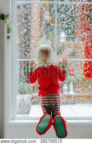 Little Girl With Blond Hair In Red And Green Christmas Pyjamas Standing Near The Big Window Looking