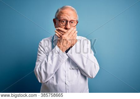 Senior grey haired doctor man wearing stethoscope and medical coat over blue background shocked covering mouth with hands for mistake. Secret concept.
