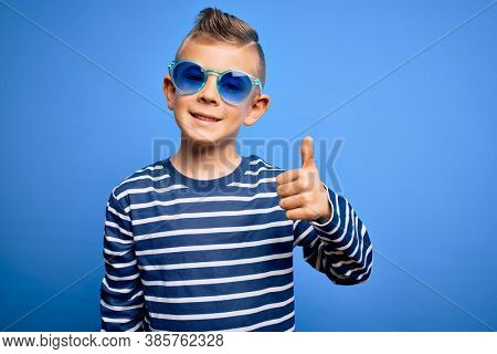 Young little caucasian kid with blue eyes standing wearing sunglasses over blue background doing happy thumbs up gesture with hand. Approving expression looking at the camera showing success.