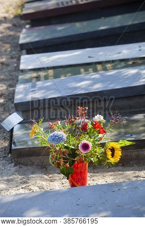 Tombstones With Flowers On A Cemetery In Rotterdam In The Netherlands