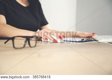 Side View Of Female Hands Using Computer On Table With Glasses And Other Stuff