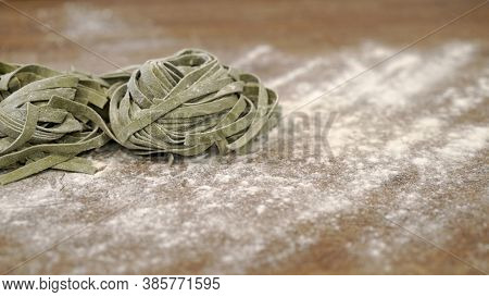 Uncooked Raw Green Italian Pasta On Wooden Table. Close Up Shot Of Raw Italian Food With Flour On Th