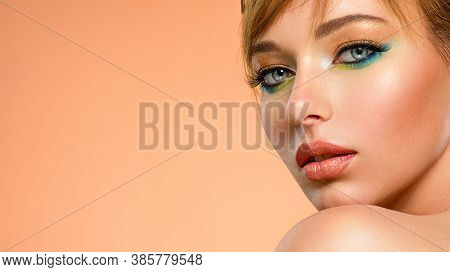 Beautiful  woman with fashion  makeup. Face of an young  woman  close-up with a green color makeup. Stylish makeup.