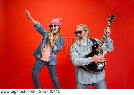 Cheerful Musician. Senior Man Spending Happy Time With Granddaughter In Neon. Joyful Elderly Lifesty