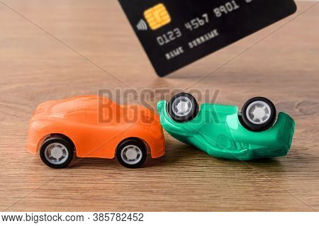Orange And Green Toy Car Crush Accident And Credit Card. Concept Of Car Buying, Renting, Service, Re