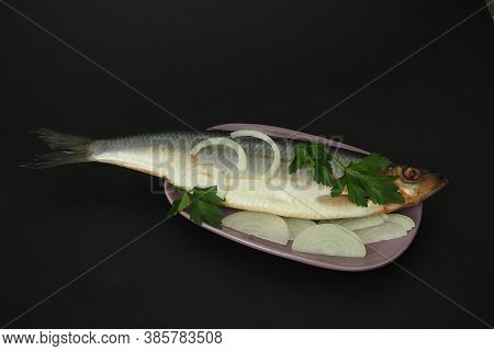 Herring Whole, Undivided With Onion And Parsley, Close-up. Fish On A Platter. Black Background.