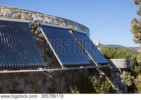 Solar Water Heating System Installed On Wall Or Roof Of House. 3 Panels Of Glass Coaxial Tubes With