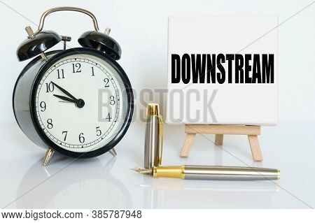 Business And Finance Concept. On The Table There Is A Clock, A Pen And A Stand With A Card On Which