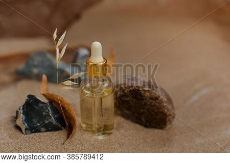 Bottle With A Pipette, Filled With Essence, Oil Or Perfume. Background Sand And Craft Paper.