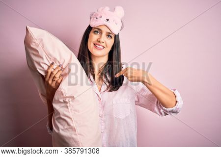 Young brunette woman with blue eyes wearing pajama hugging bed pillow at night time with surprise face pointing finger to himself