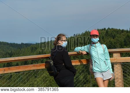 Two Women Observe The Surrounding Nature From The Handrail Of The Tower