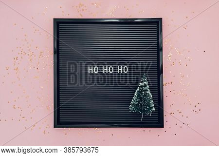 Words Ho Ho Ho On Letterboard With Christmas Tree On Pink Background With Glitter Confetti. New Year