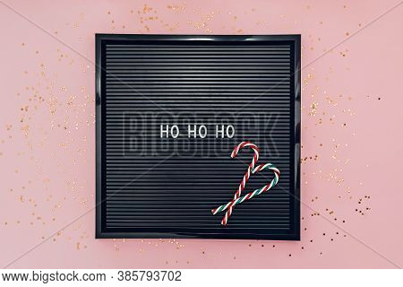 Words Ho Ho Ho On Letterboard With Candy Canes On Pink Background With Glitter Confetti. New Year Co