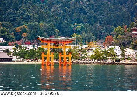 The Itsukushima Shrine Otorii Gate from the water at Miyajima Island, Hiroshima, Japan. (sign reads: Itsukushima Shrine)