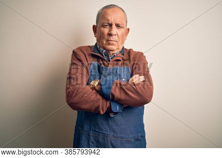 Senior handsome baker man wearing apron standing over isolated white background skeptic and nervous, disapproving expression on face with crossed arms. Negative person.