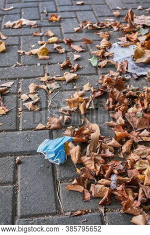 Discarded Protective Medical Face Mask Against Covid-19 Coronavirus Pandemic With Fallen Autumn Leav