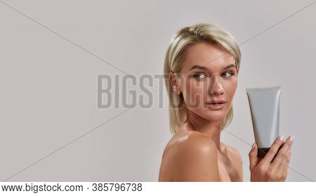 Portrait Of Young Woman With Perfect Fresh Skin Looking Aside, Holding Cosmetic Skincare, Bodycare P
