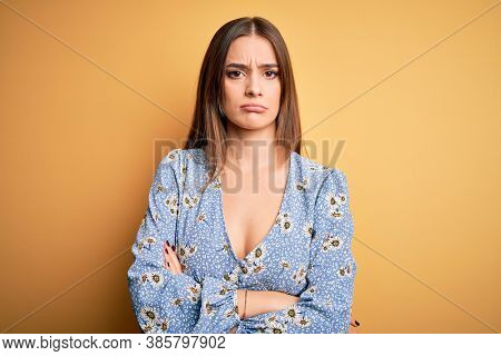 Young beautiful brunette woman wearing casual floral t-shirt standing over yellow background skeptic and nervous, disapproving expression on face with crossed arms. Negative person.