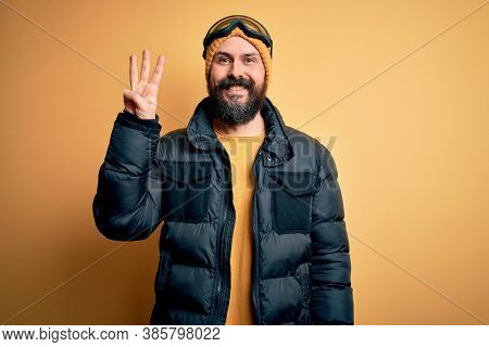 Handsome skier bald man with beard skiing wearing snow sportswear and ski goggles showing and pointing up with fingers number three while smiling confident and happy.