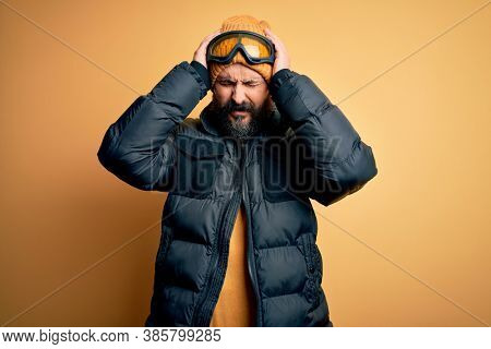 Handsome skier bald man with beard skiing wearing snow sportswear and ski goggles suffering from headache desperate and stressed because pain and migraine. Hands on head.