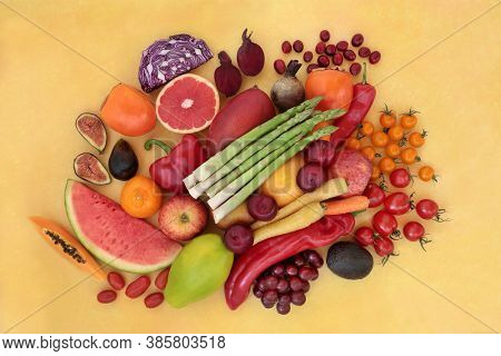 Healthy diet fruit & vegetables high in lycopene for an immune system boost with super foods also high in anthocyanins, antioxidants, vitamins, minerals & dietary fibre. Flat lay on mottled yellow.