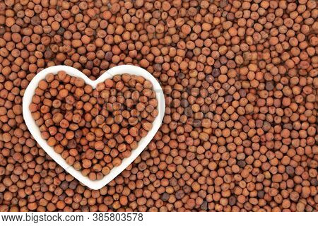 Carlin peas healthy heart food in a white porcelain heart shaped dish & forming an abstract background. Very high in protein, low in fat, high in fibre, antioxidants & anthocyanin with low GI.