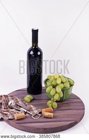 Wine Bottle And Grapes On An Old Wine Barrel Top View Close Up.wine Accessories On Dark Wooden Round