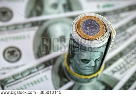 One Real Coin On A Pack Or Roll Of American Money. Concept Of Devaluation Of The Real Against The Do