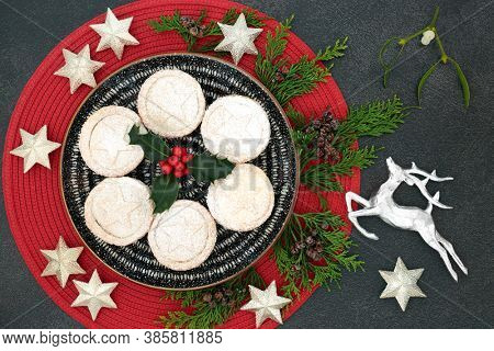 Delicious Christmas mince pies on a plate with winter berry holly, cedar cypress, mistletoe, silver star & reindeer decorations on grey grunge  background. Festive food composition. Top view.