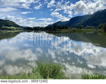 Ossiacher Lake In Carinthia, Austria On A Summer Day With Great Cloudscape Being Reflected In The La