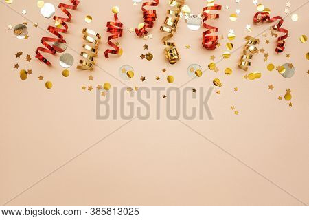 Gold And Red Christmas Ribbons And Confetti On A Pink Background. Christmas Or New Year Conceptual B