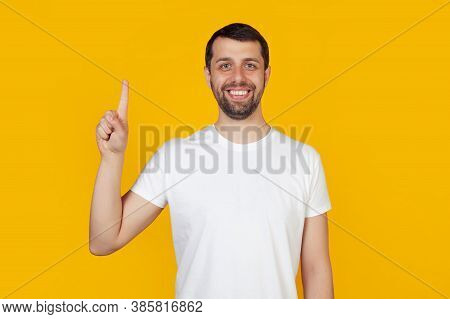 Modern Young Man With A Beard In A White Tank Top Shows Number One With Fingers On Hand, Smiling Con