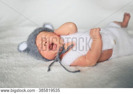 Cute Crying Newborn Little Baby Boy Sleeping In Crib In A Knitted Suit With Ears. Baby Goods Packagi