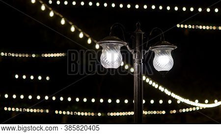Black Iron Lamppost With Two Lamps With A Glass Shade Glows With White Light In The Background A Str