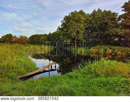 Place For Fishing On Creek. Summer Background With Forest On Riverbank